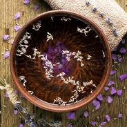 4594485-bowl-of-pure-water-and-lavender-petals-on-the-old-wooden-surface-spa-treatments-composition